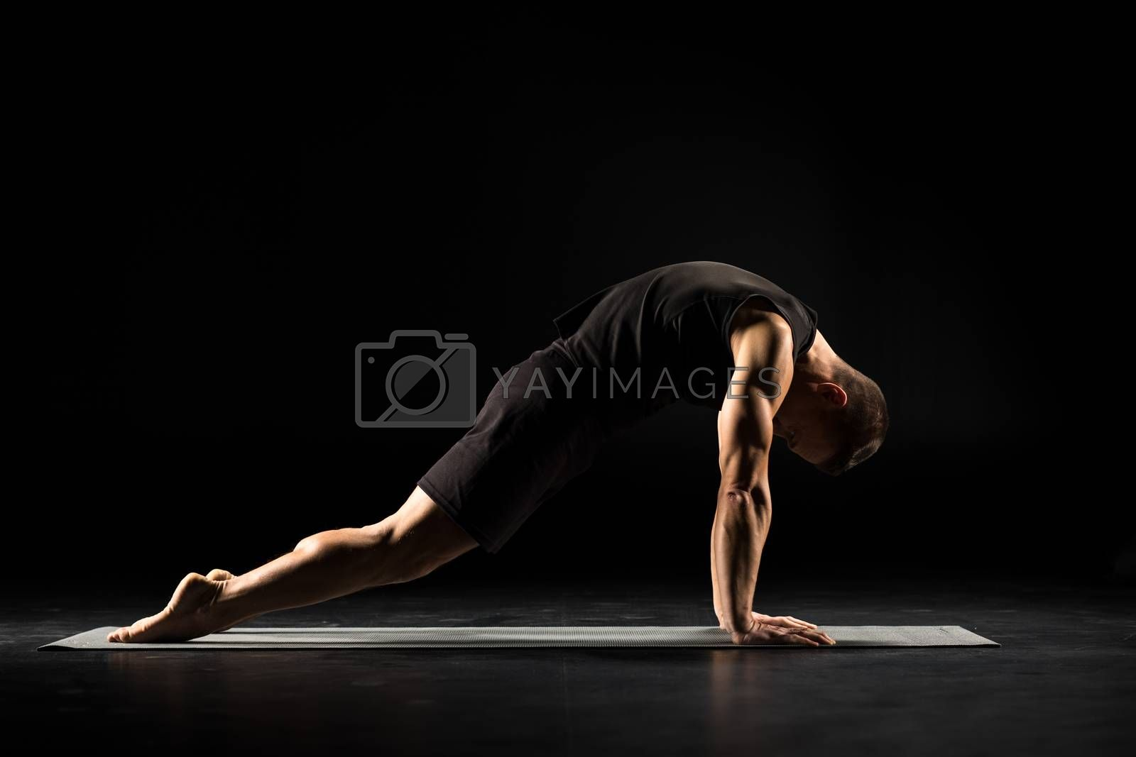 Man practicing yoga performing asana marjariasana on yoga mat