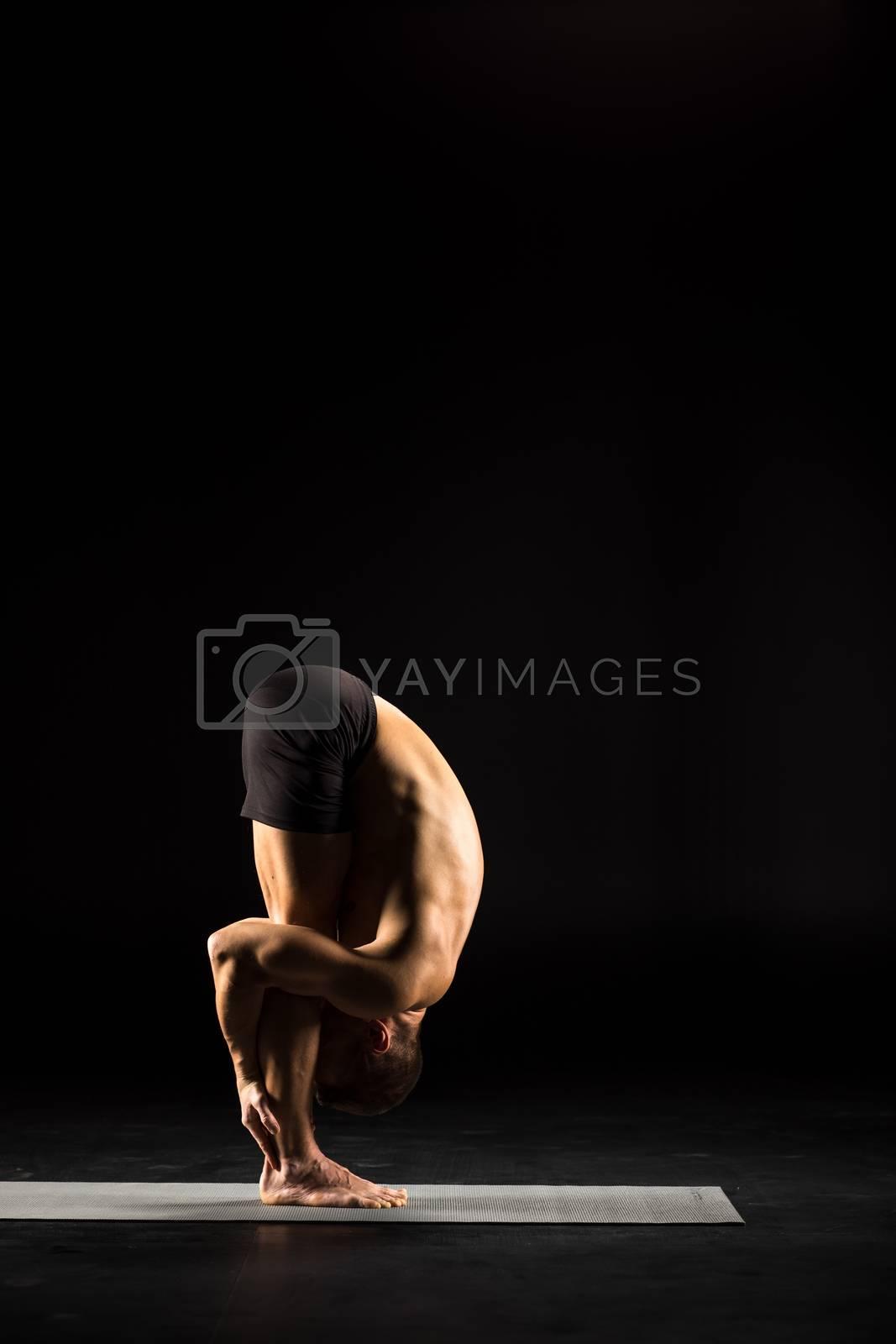 Man performing Uttanasana on yoga mat