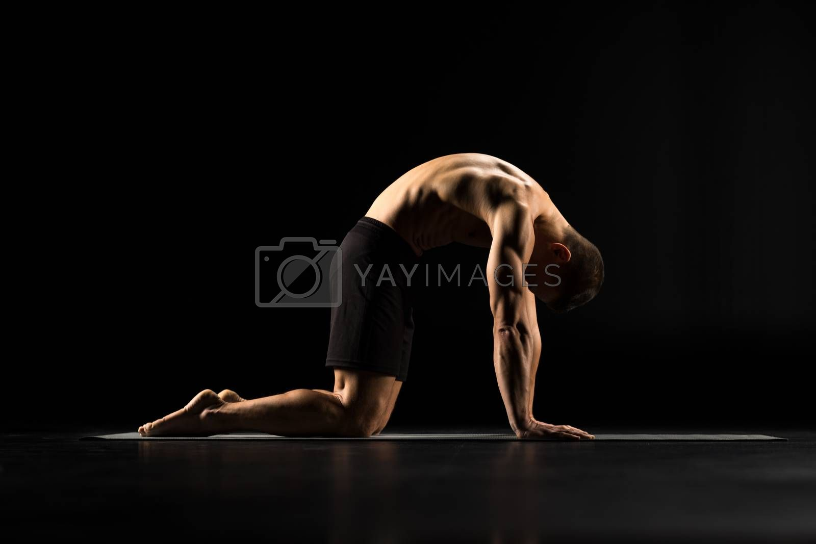 Man performing Marjariasana or Cat Pose on yoga mat