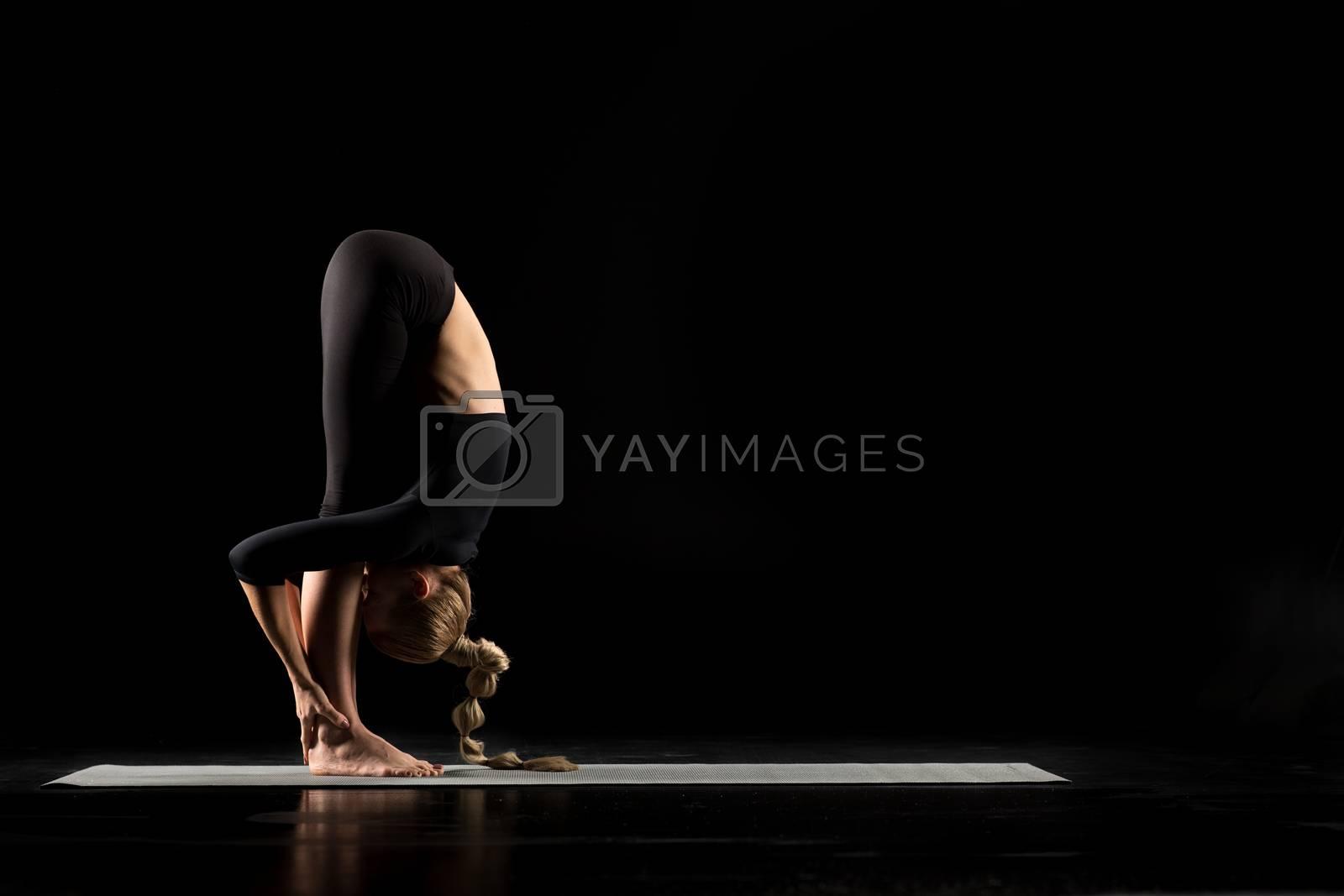 Woman performing Uttanasana on yoga mat