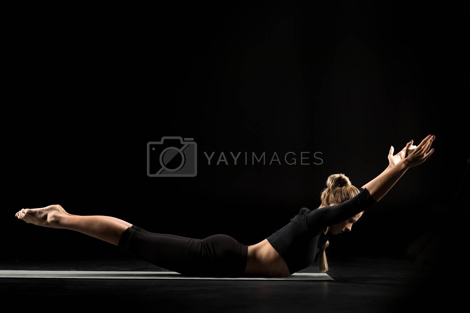 Woman lying in yoga position by LightFieldStudios