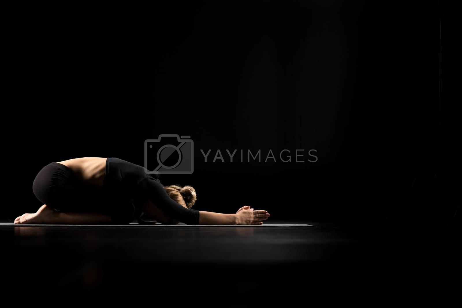 Woman performing Balasana or Childs Pose on yoga mat