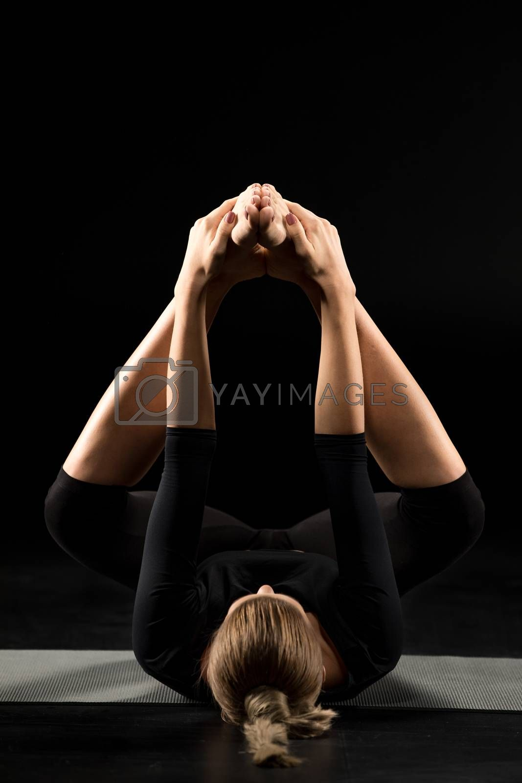 Woman performing variation of Ananda Balasana on yoga mat