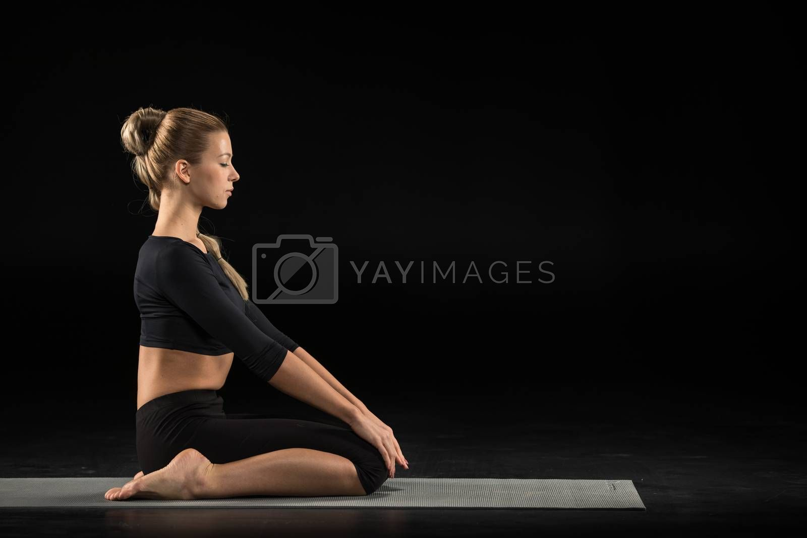 Woman sitting in yoga position by LightFieldStudios