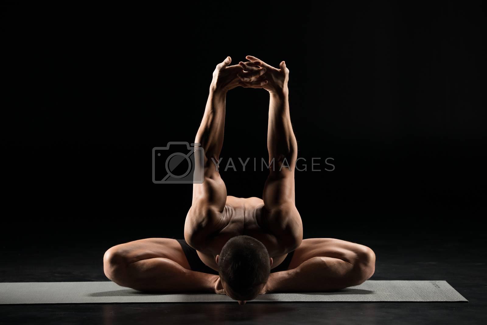 Man performing Dwikonasana while sitting on yoga mat