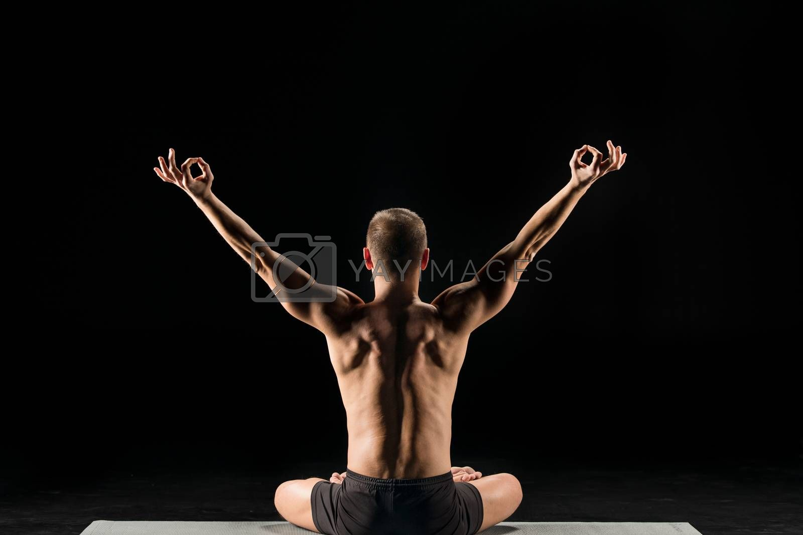 Rear view of man practicing yoga and meditating on yoga mat