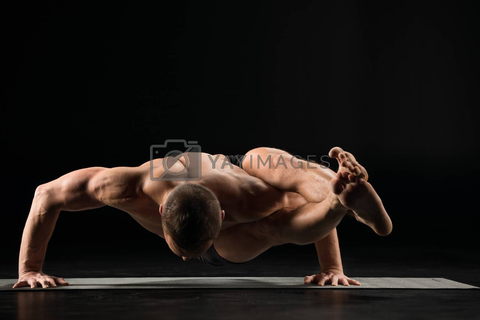 Young man practicing yoga doing an asana astavakrasana on yoga mat