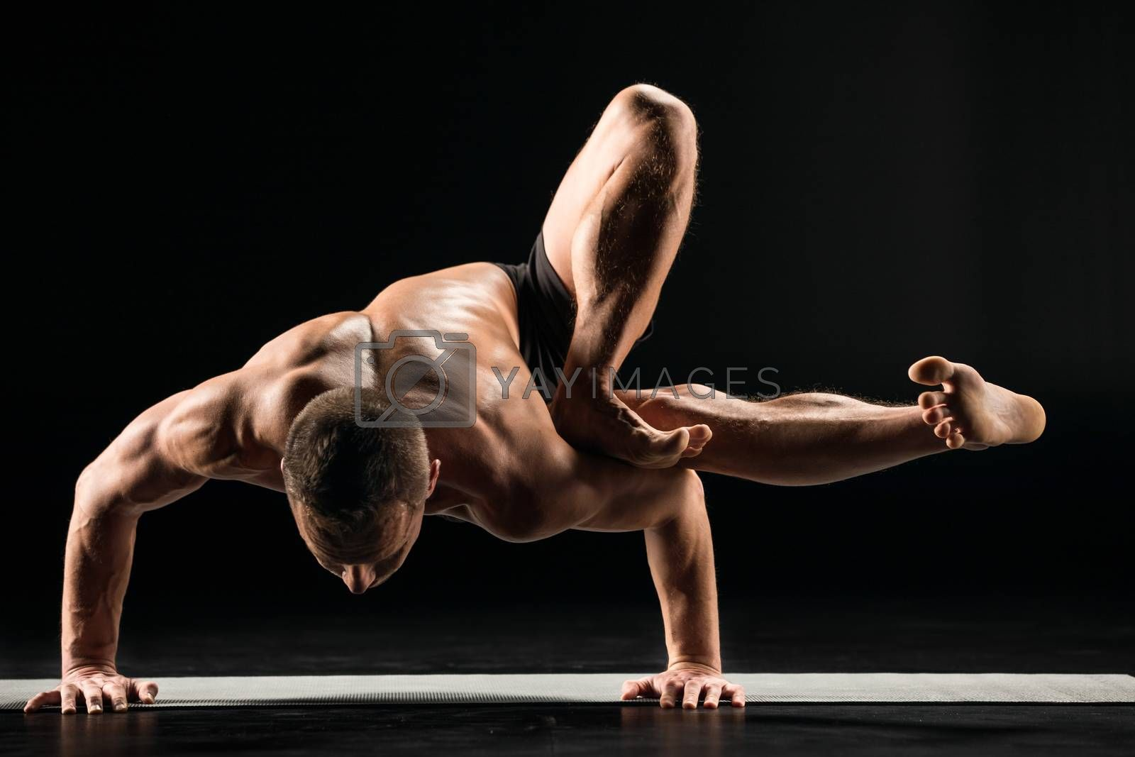 Young man practicing yoga doing an asana astavakrasana or hand standing pose on yoga mat
