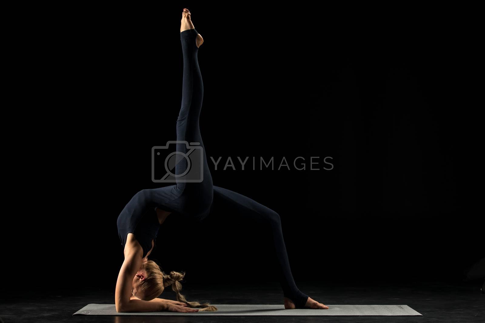 Woman practicing yoga performing Bridge pose (Ekopada Dhanurasana) on yoga mat
