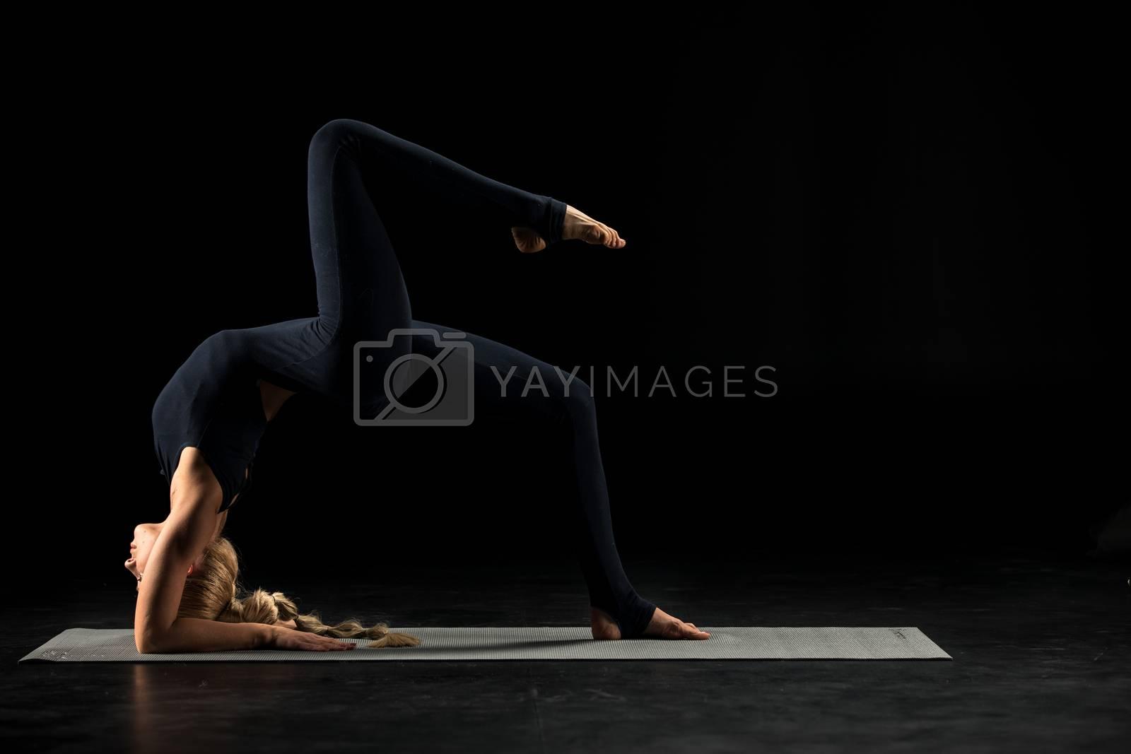 Woman standing in yoga position       by LightFieldStudios