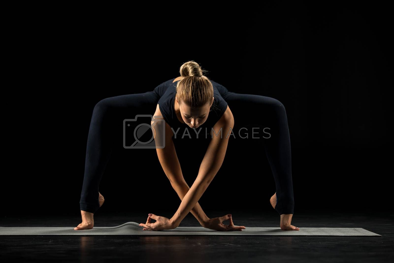 Woman practicing yoga standing in Forward Bending variation of Goddess, Temple or Sumo Squat Pose