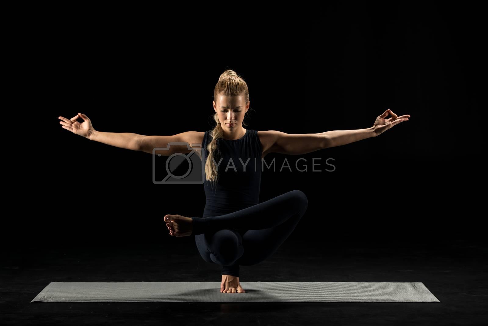 Woman practicing yoga performing squat pigeon pose on yoga mat