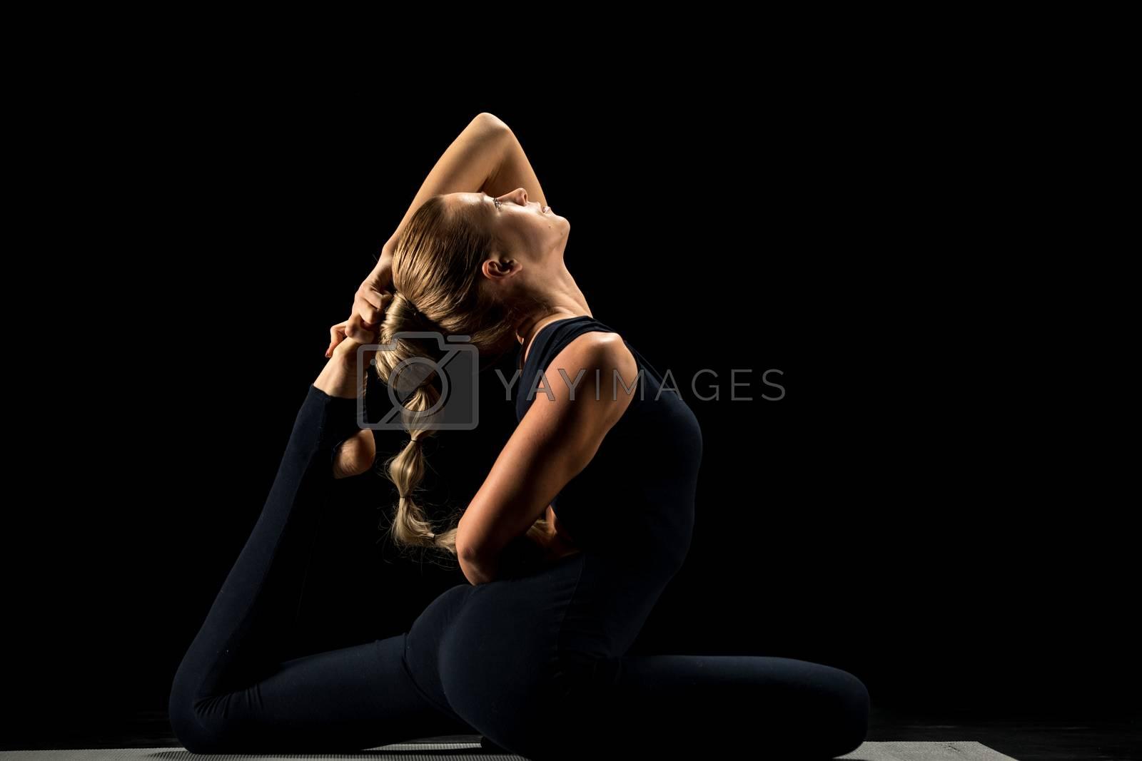 Woman practicing yoga sitting in One Legged King Pigeon Posture (Eka Pada Rajakapotasana)