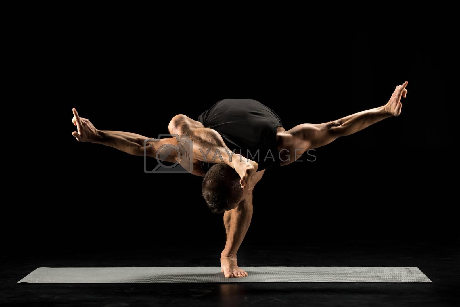 Man performing Pada Sirsasana on yoga mat