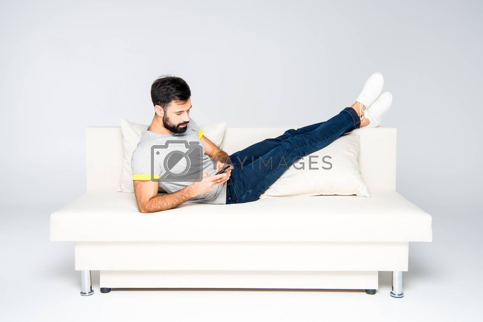 Bearded man lying on white couch and using smartphone