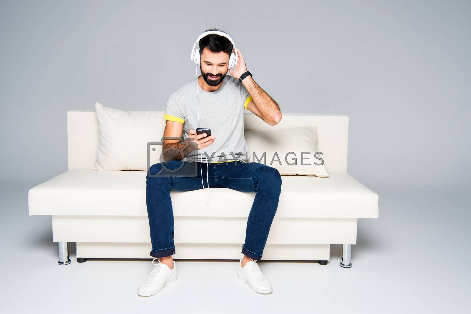 Bearded man in white headphones sitting on couch and listening music with smartphone