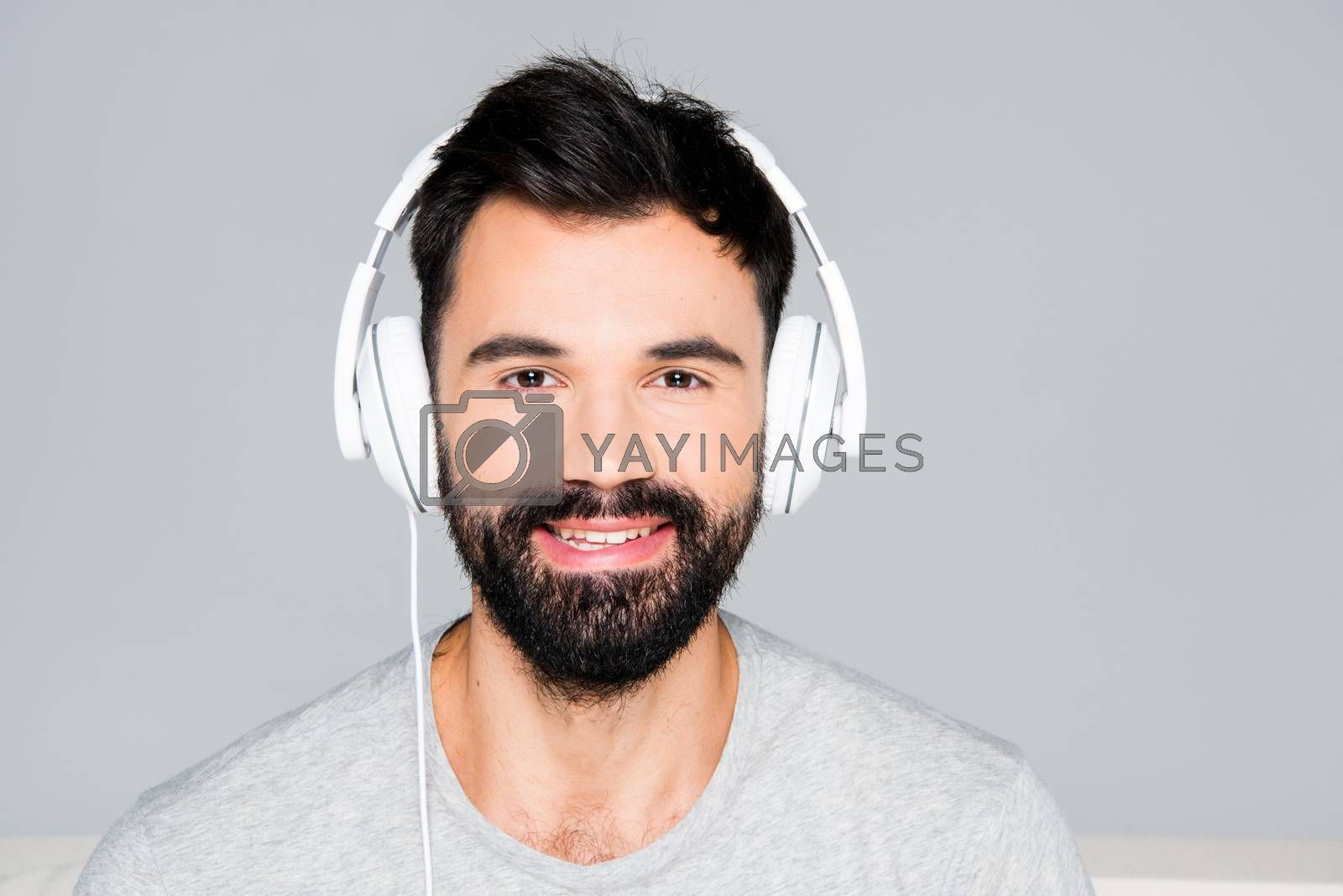 Portrait of bearded man in white headphones looking at camera