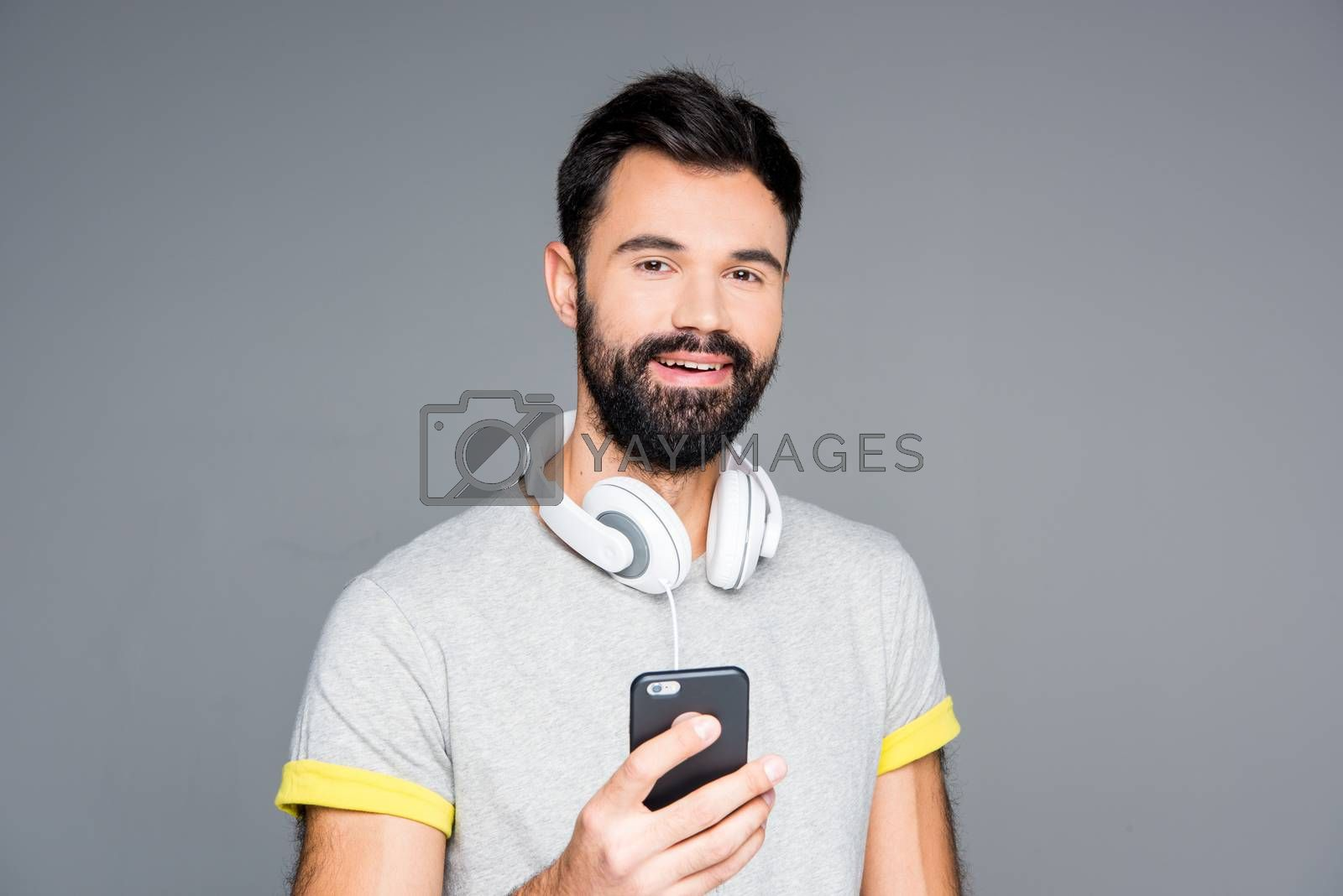 Smiling bearded man using smartphone and looking at camera on grey
