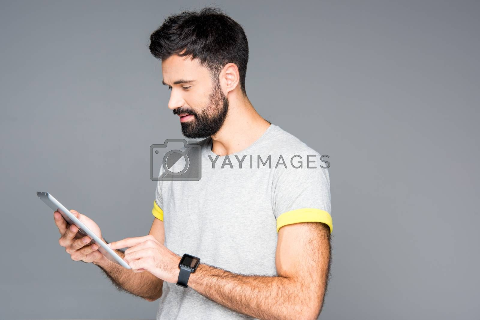 Smiling bearded man using digital tablet on grey