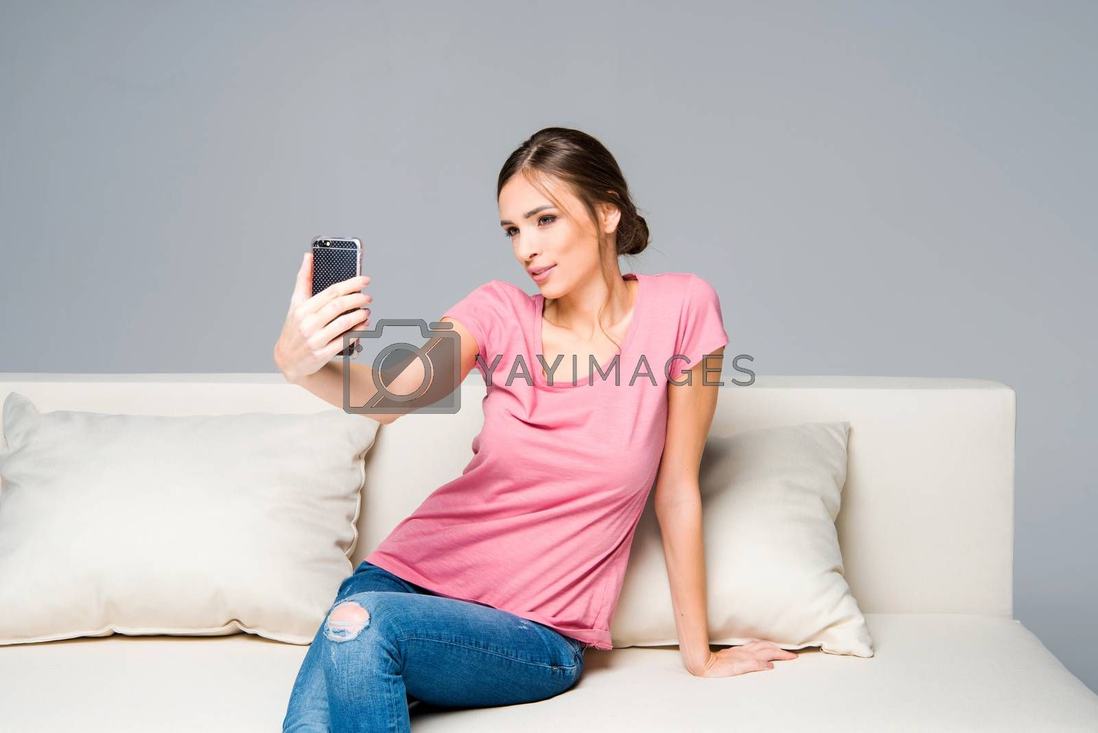 Smiling young woman sitting on white couch and taking selfie
