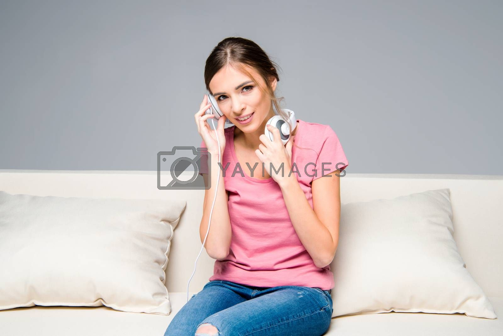 Smiling young woman with white headphones sitting on couch and looking at camera