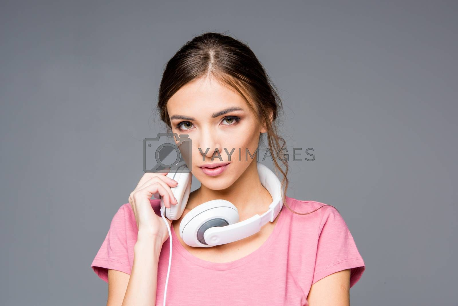 Smiling young woman with white headphones looking at camera on grey
