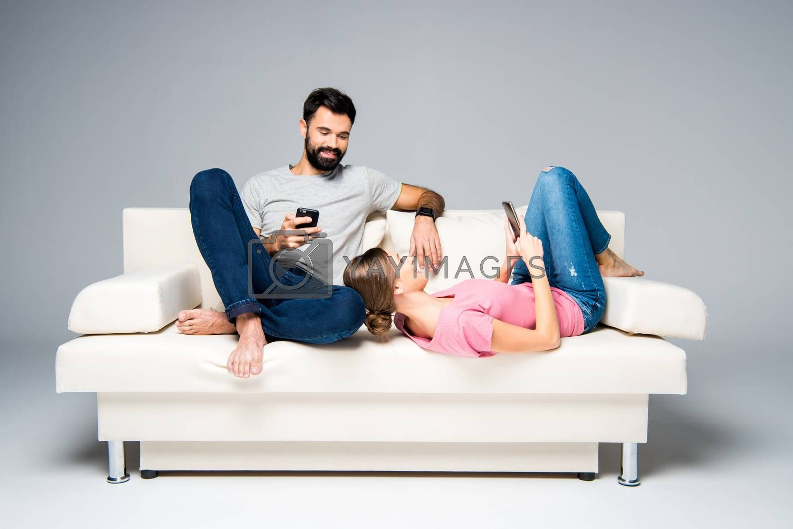 Young couple resting on white couch and using smartphones