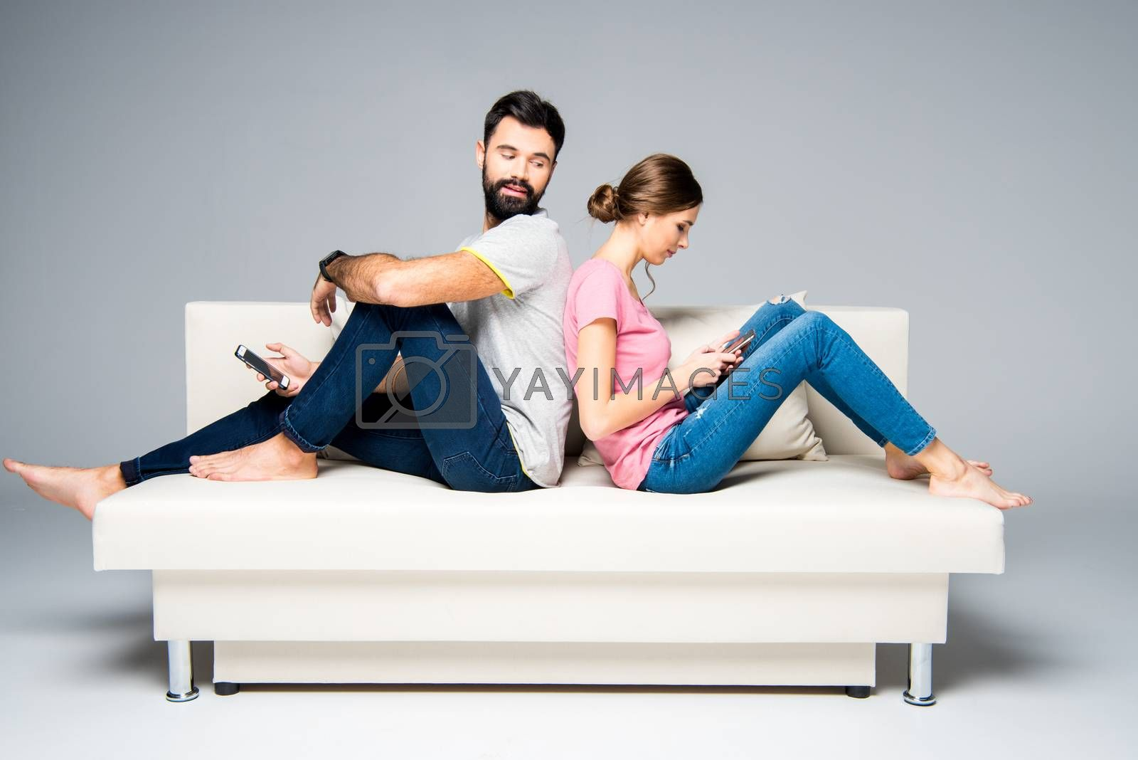Young couple sitting back to back on white couch and using smartphones
