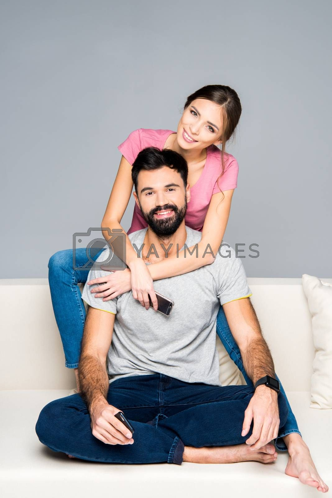 Happy couple hugging on couch and looking at camera