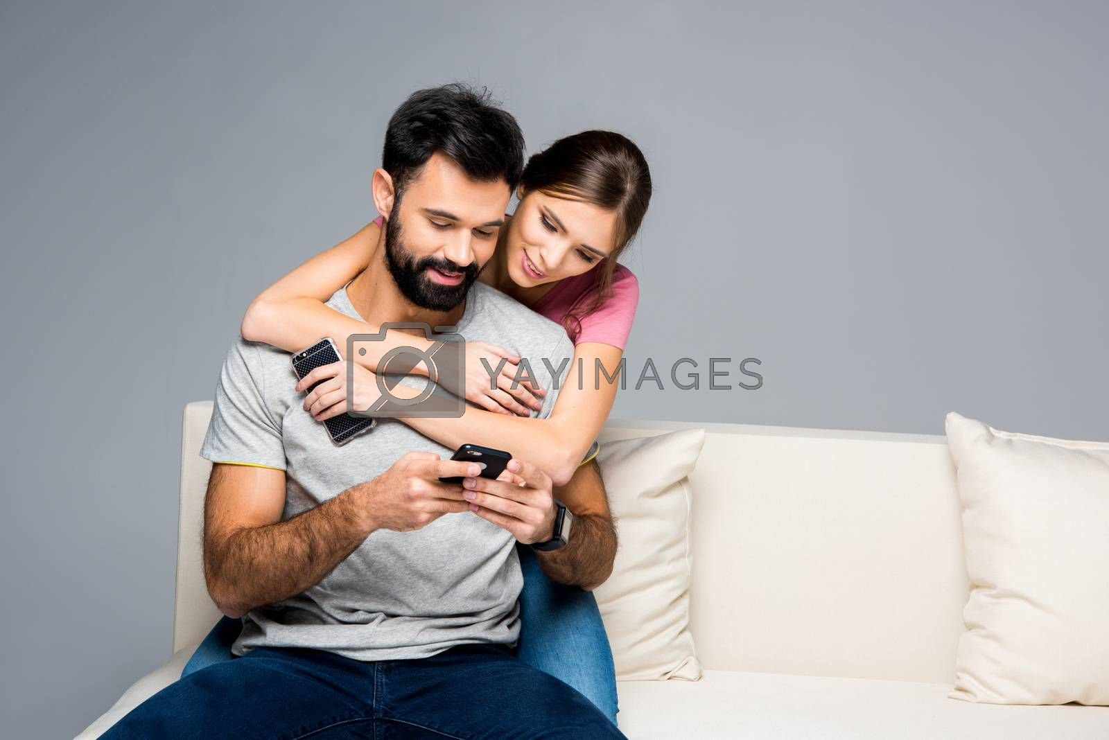 Young couple hugging on white couch and using smartphones