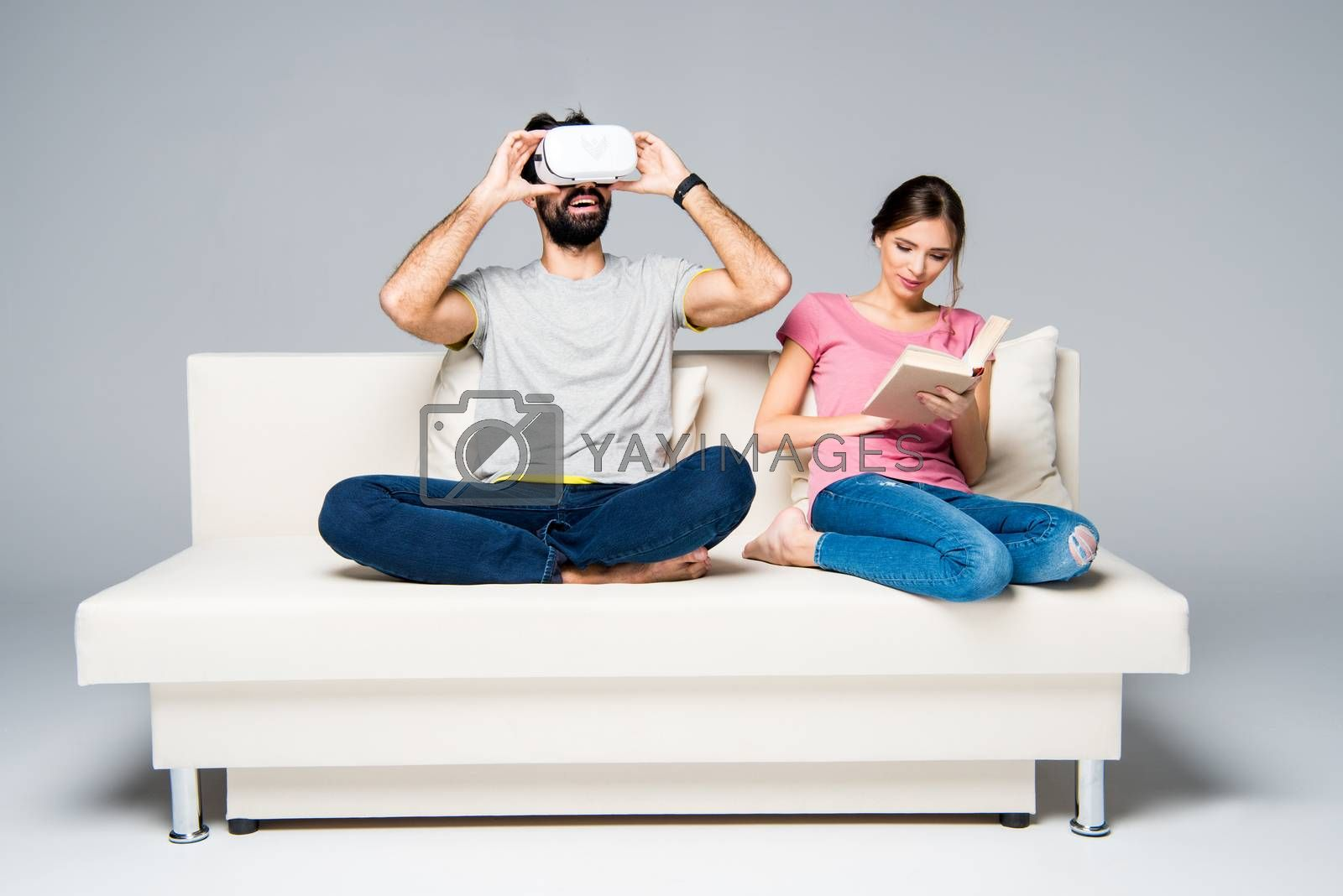 Couple resting on white couch, woman reading book and man using virtual reality headset