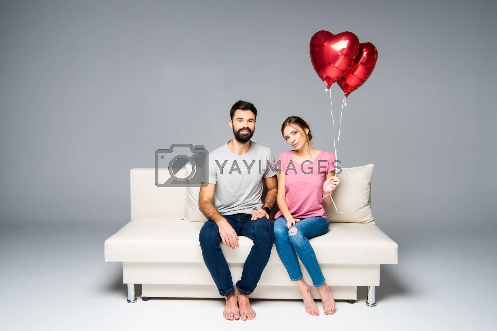 Couple sitting on white couch with red heart-shaped balloons