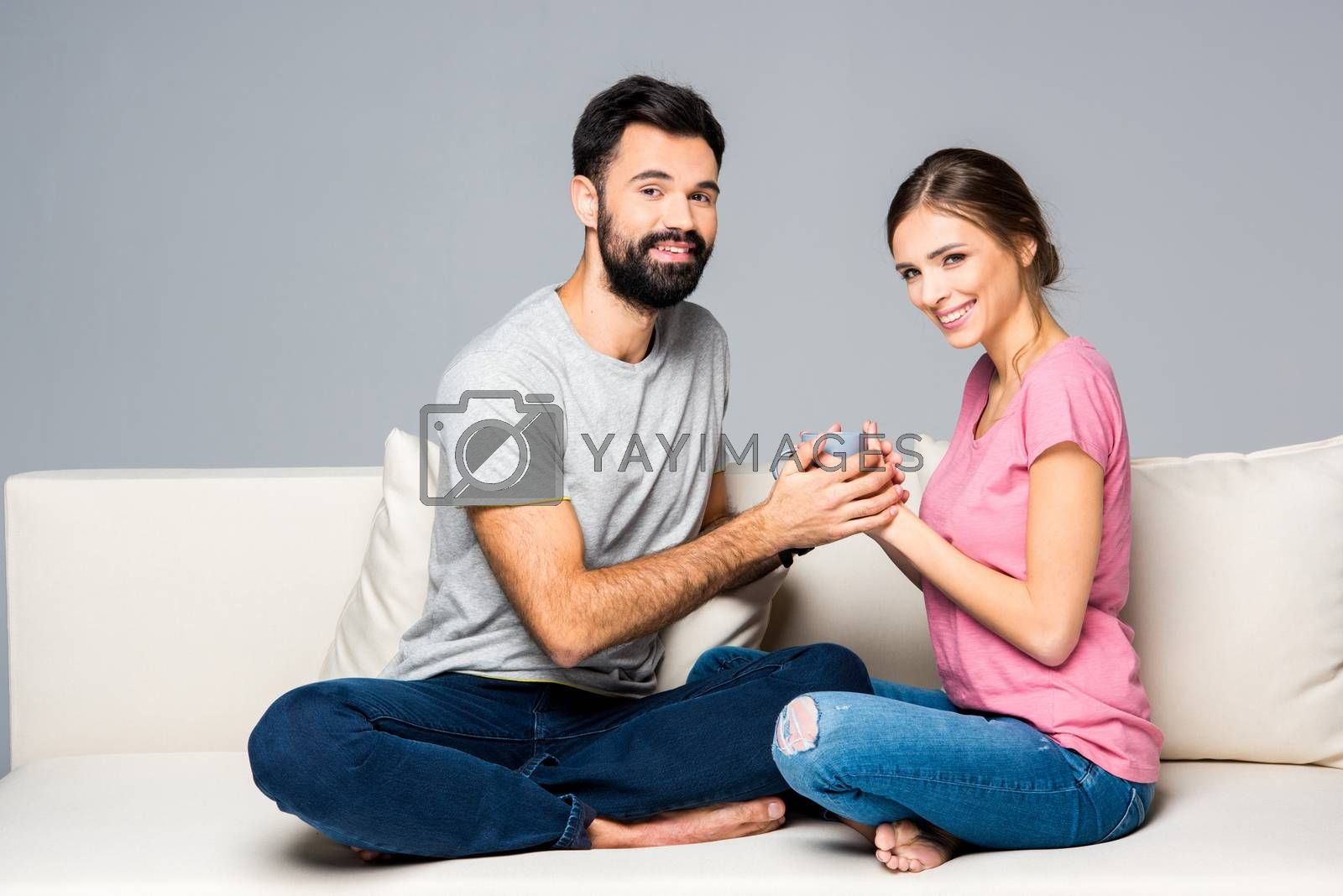 Smiling couple sitting on couch and holding cup