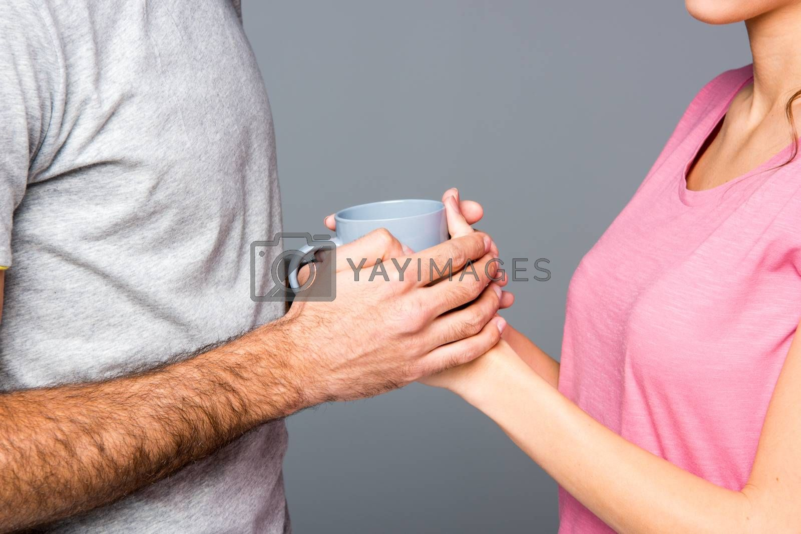 Partial view of couple holding cup on grey