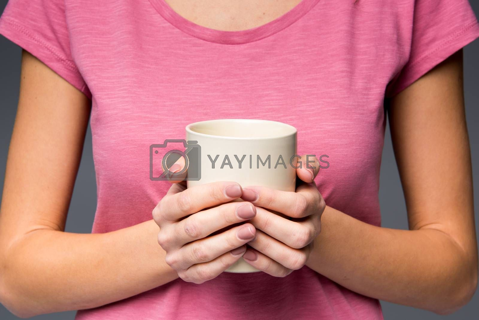 Woman holding white cup and looking at camera on grey