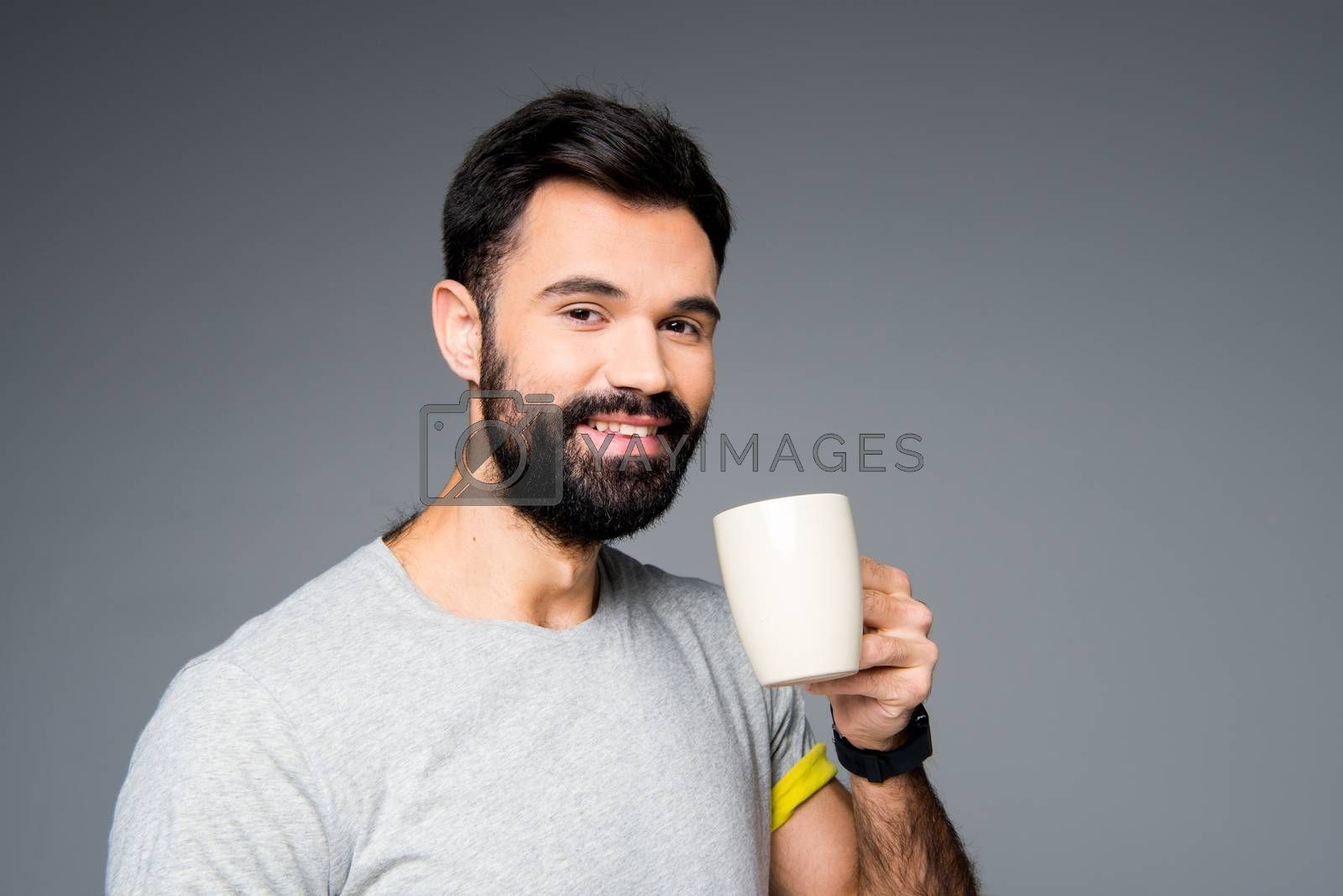 Man holding white cup and looking at camera on grey