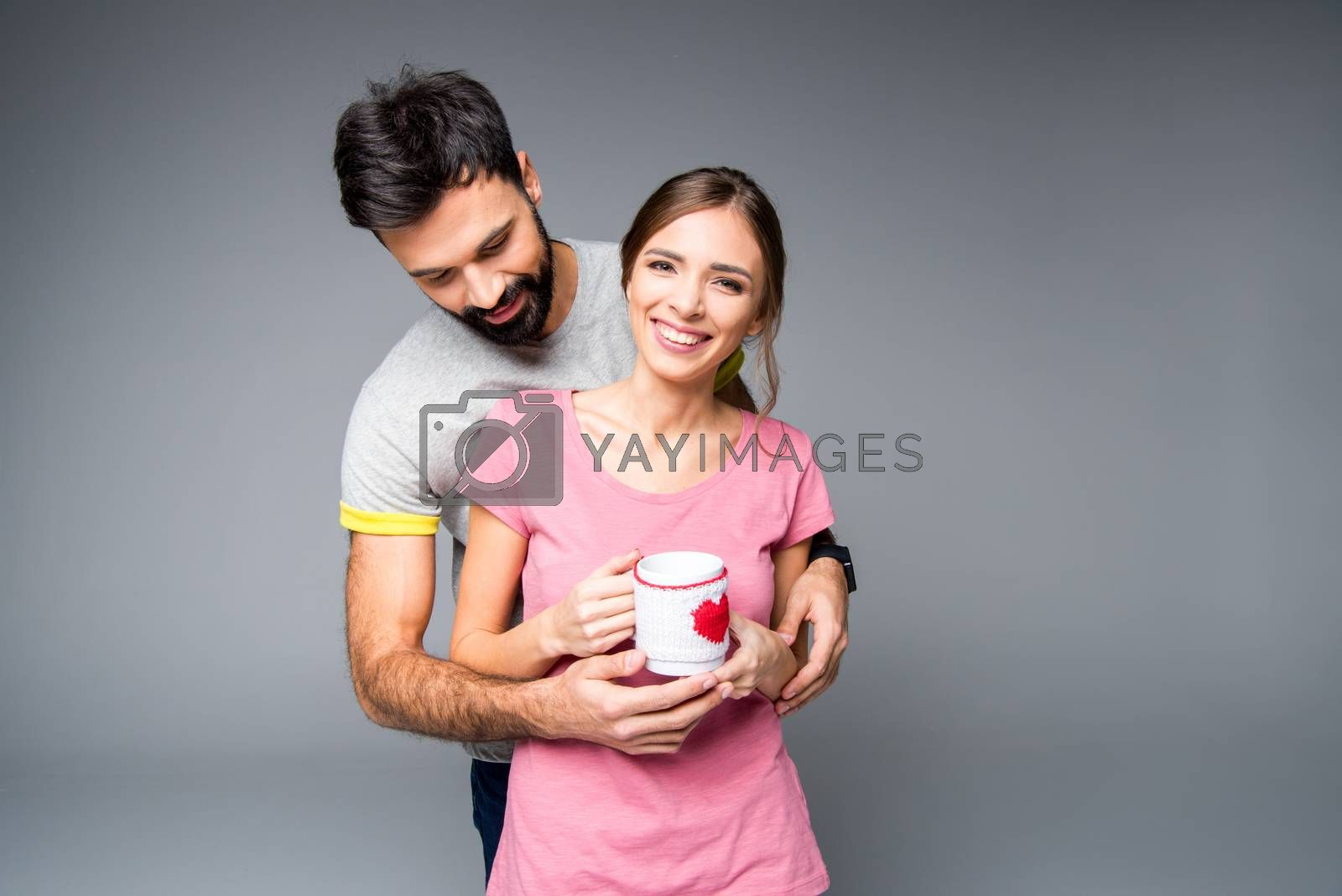 Happy couple hugging and holding cup on grey