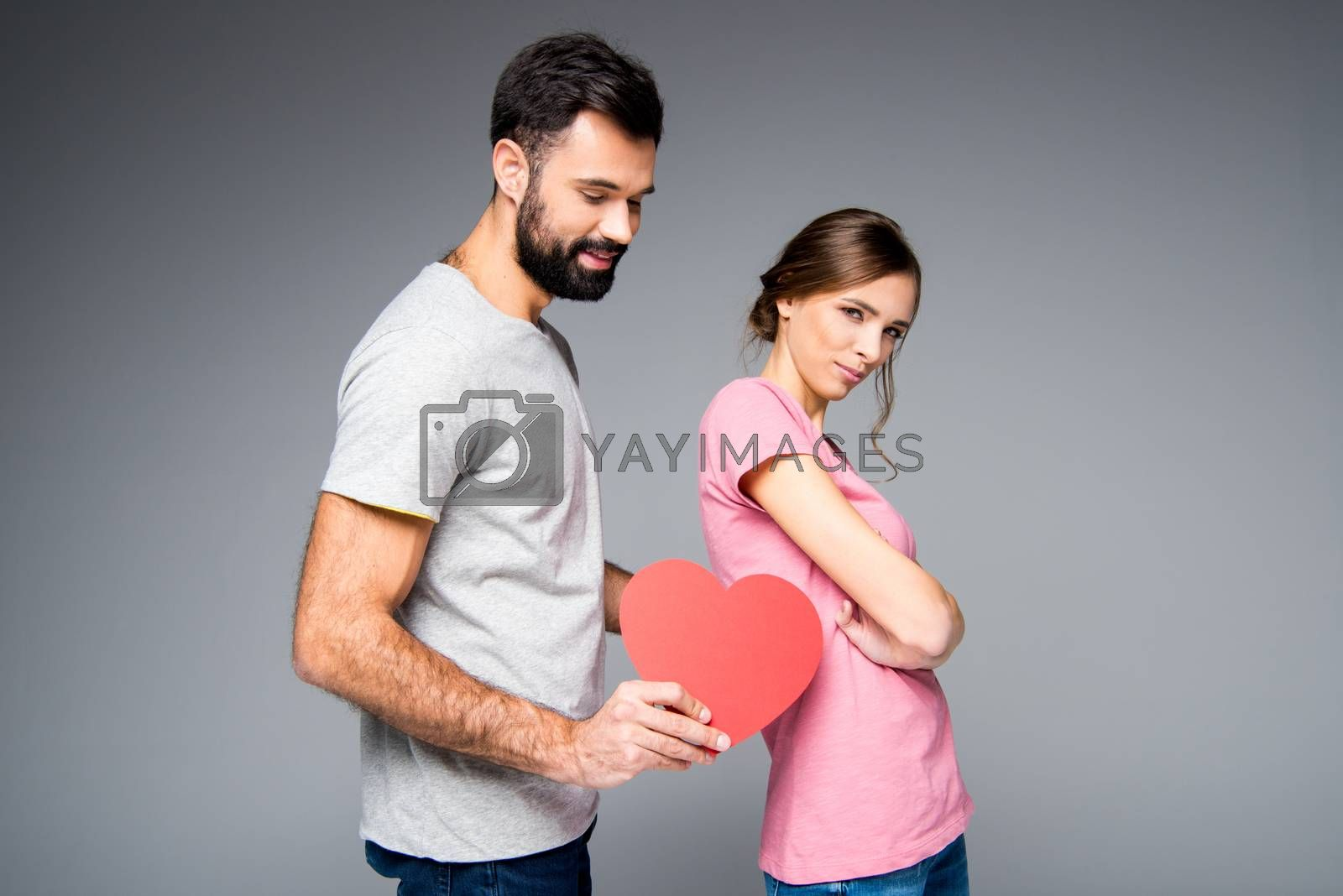 Young couple posing with red paper heart on grey