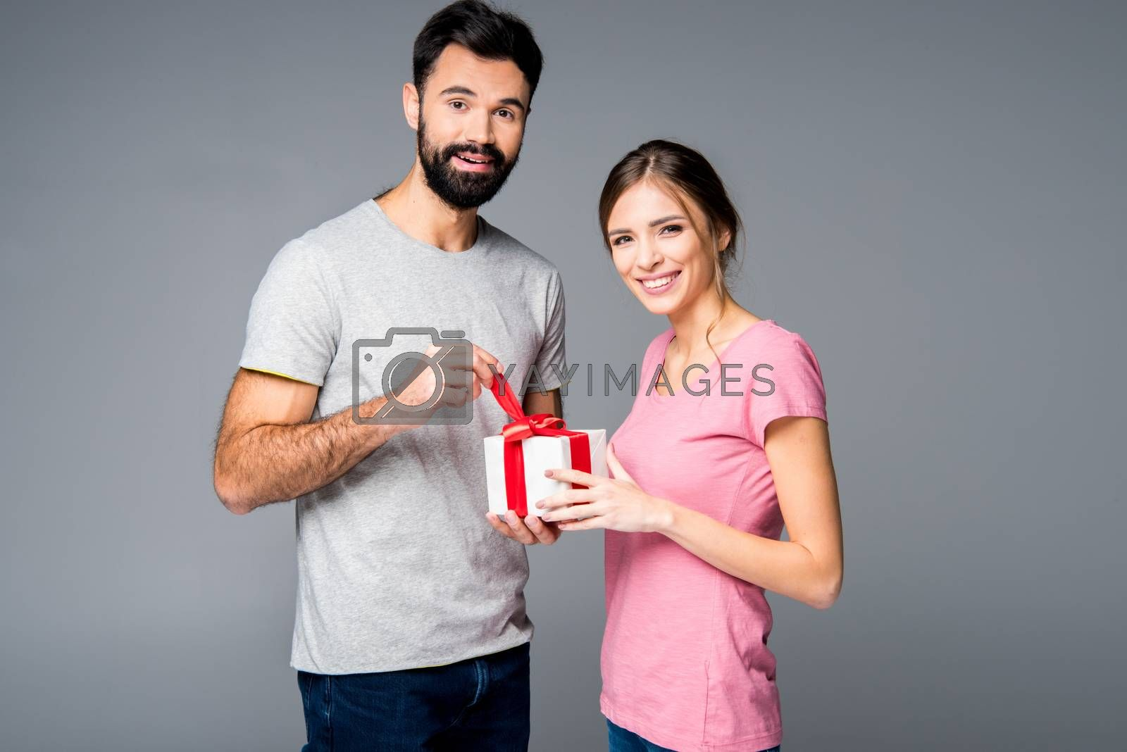 Happy couple standing with gift box and looking at camera on grey