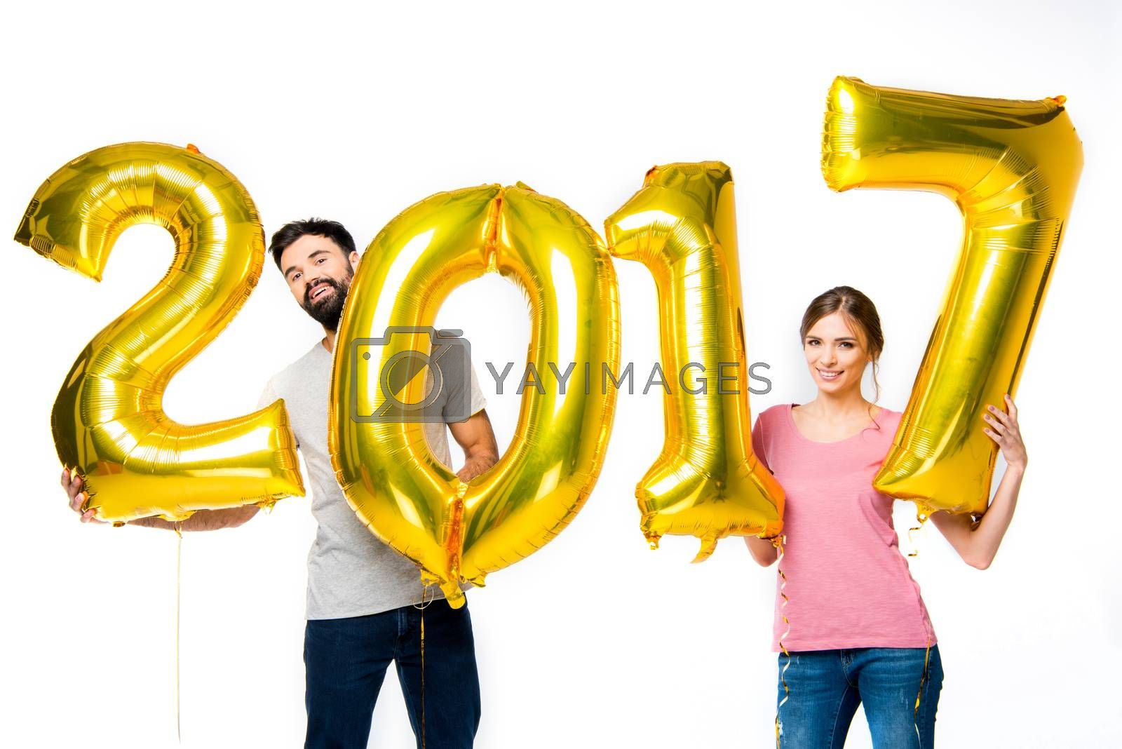 Happy couple holding golden 2017 sign balloons and looking at camera on white