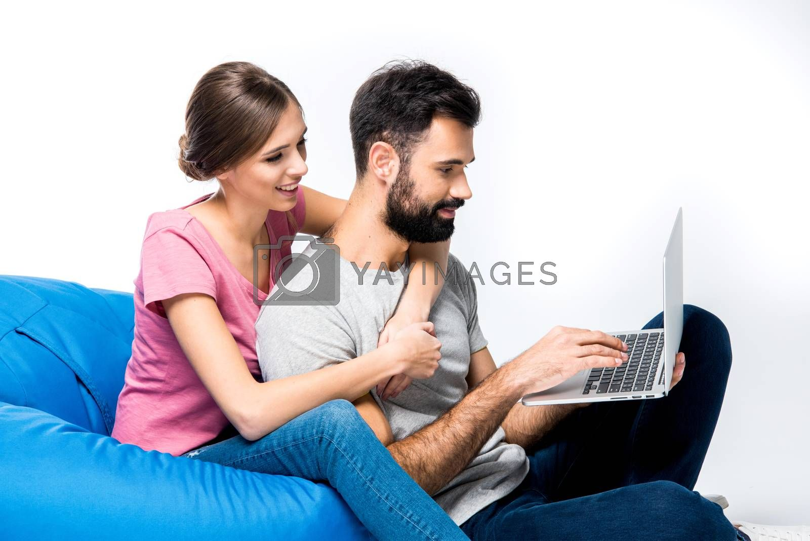 Young couple sitting on big blue pouf and using laptop, on white