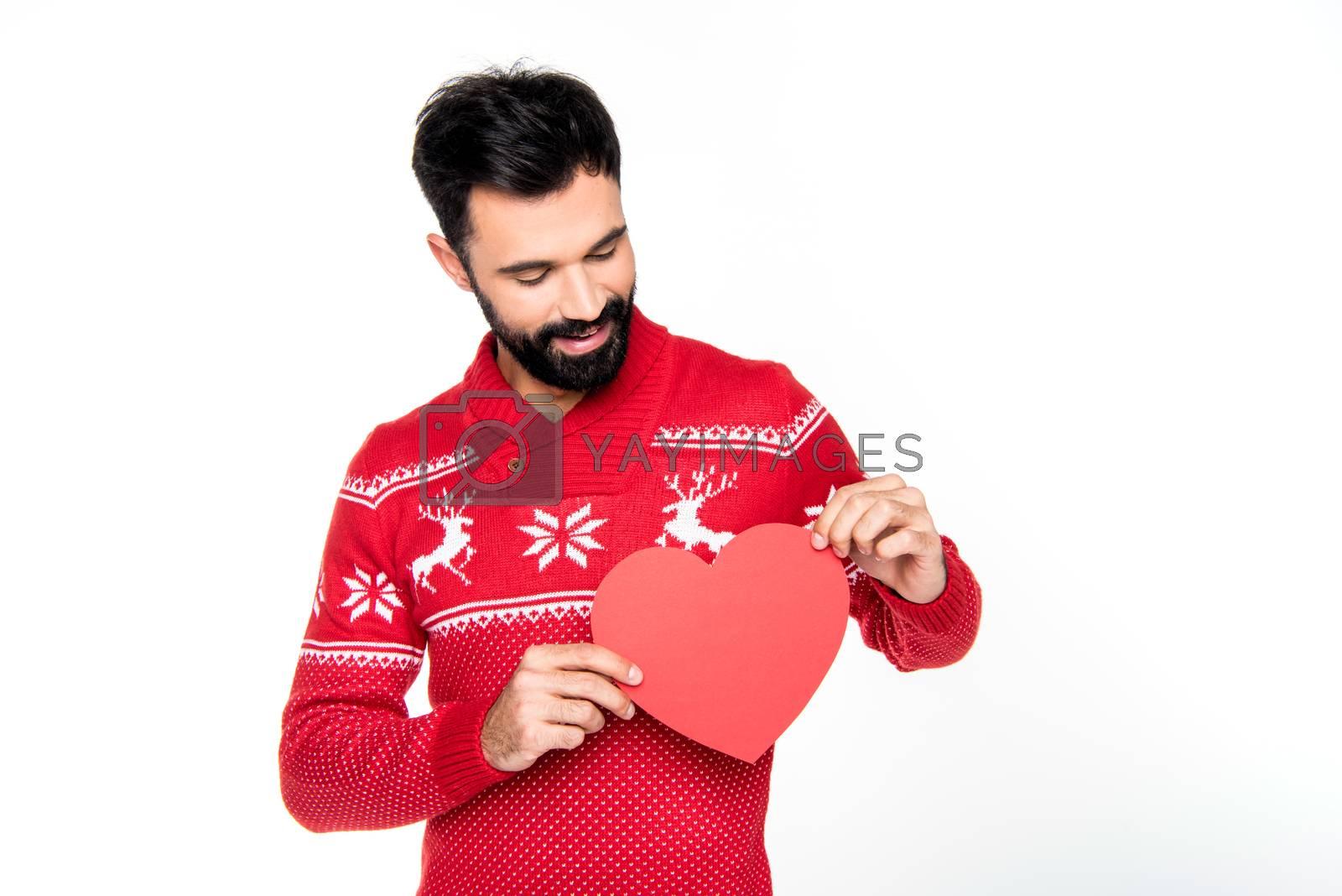 Smiling bearded man holding red paper heart on white