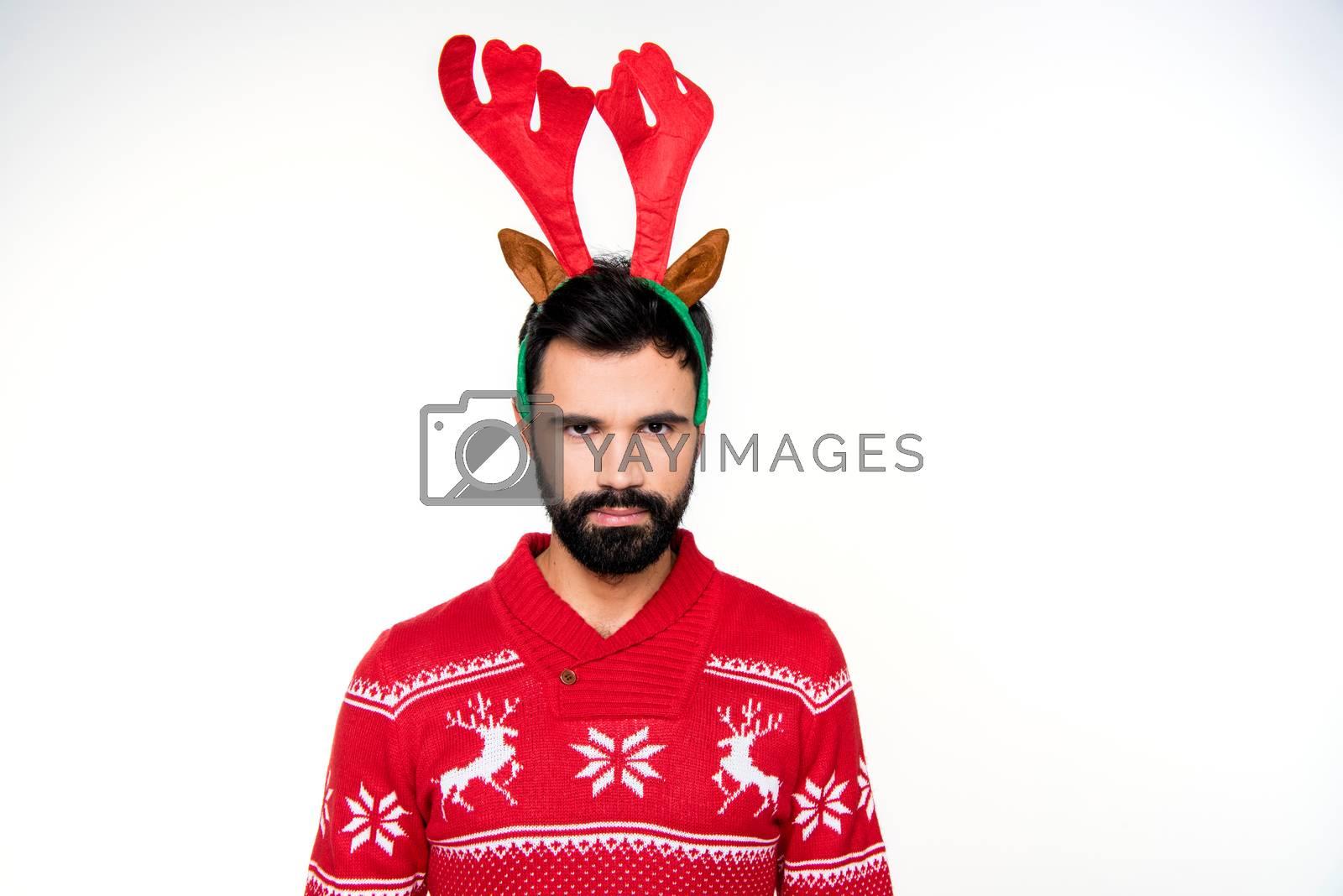 Serious bearded man in reindeer antlers headband looking at camera on white