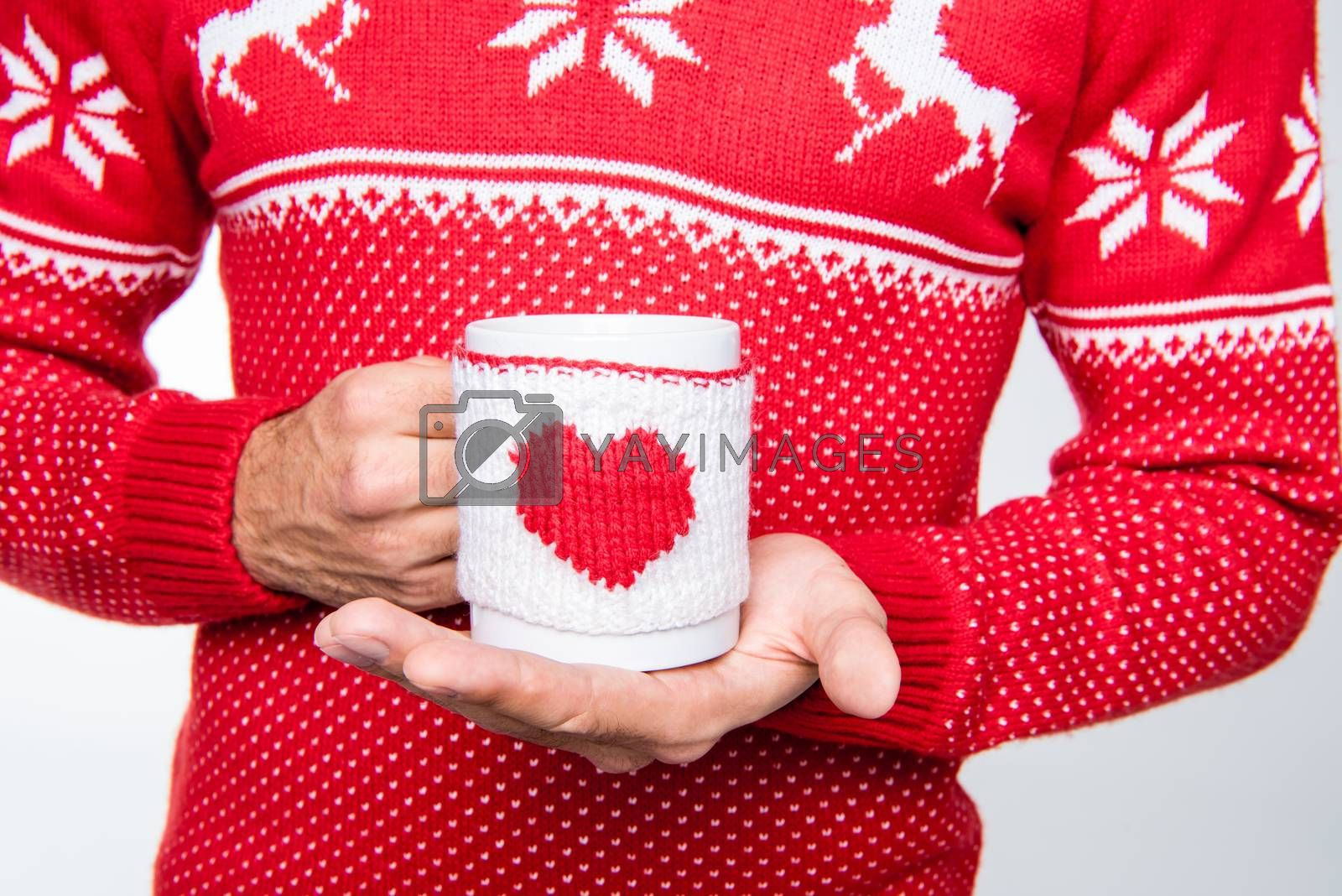 Partial view of man in red knitted sweater holding cup with hot drink