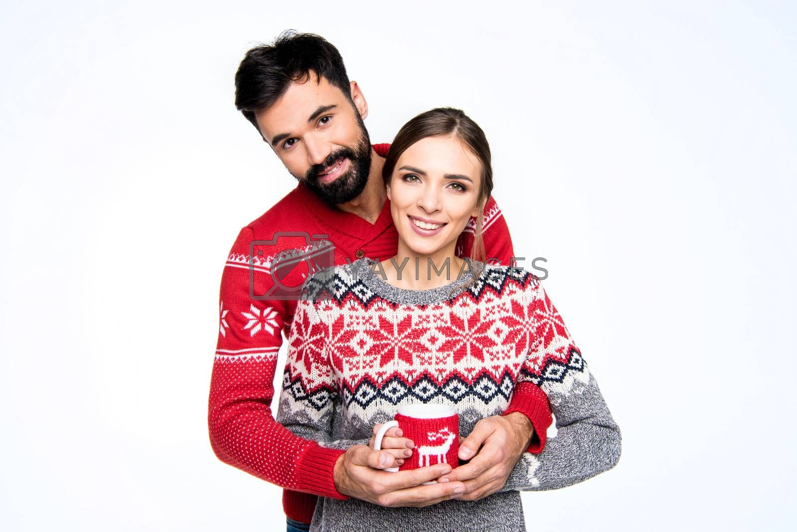Smiling couple in knitted sweaters holding cup with hot drink