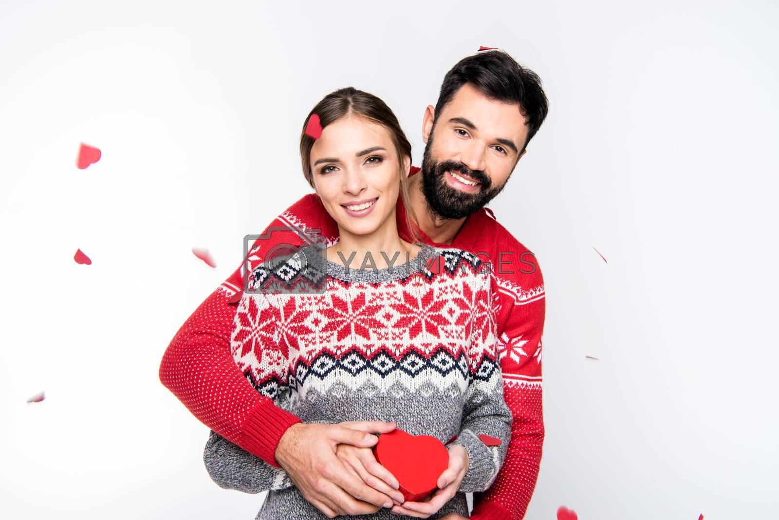 Hugging couple with red heart, standing on white