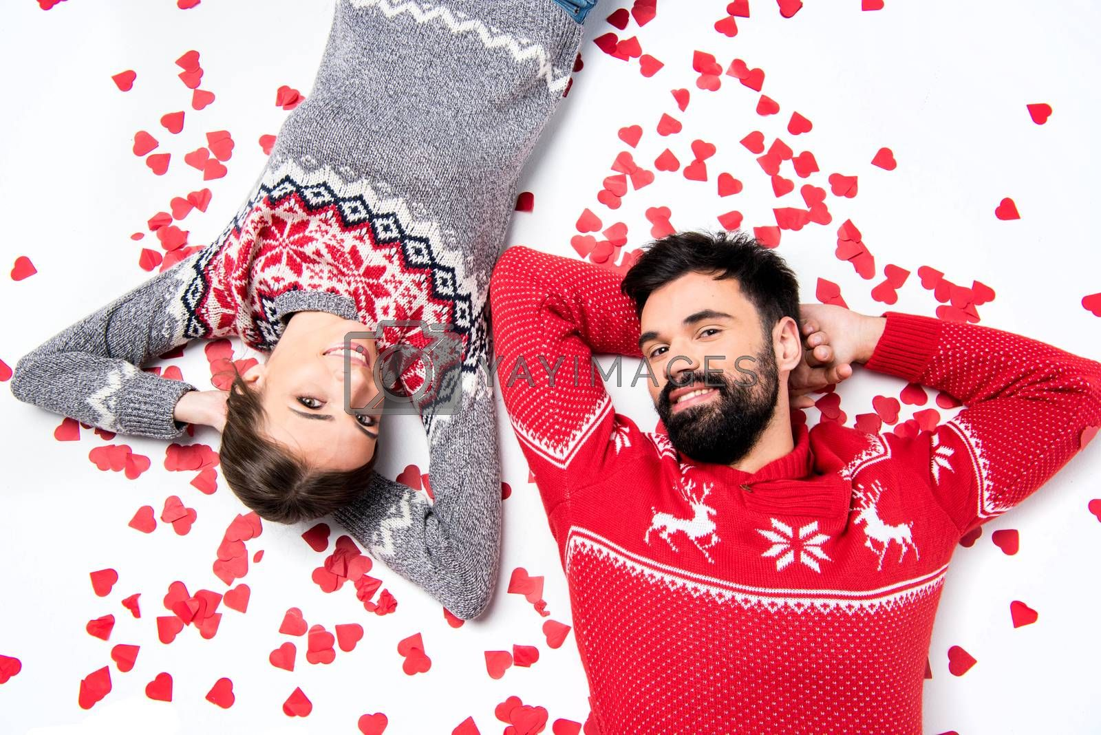 Loving couple lying together on white floor with pile of red hearts