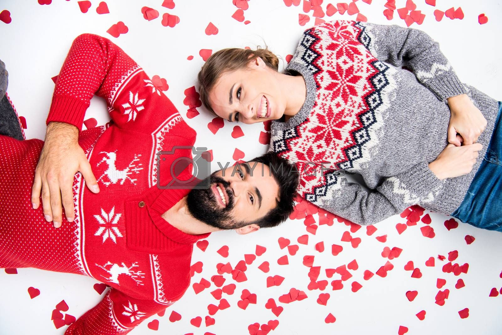 Royalty free image of couple lying with hearts by LightFieldStudios