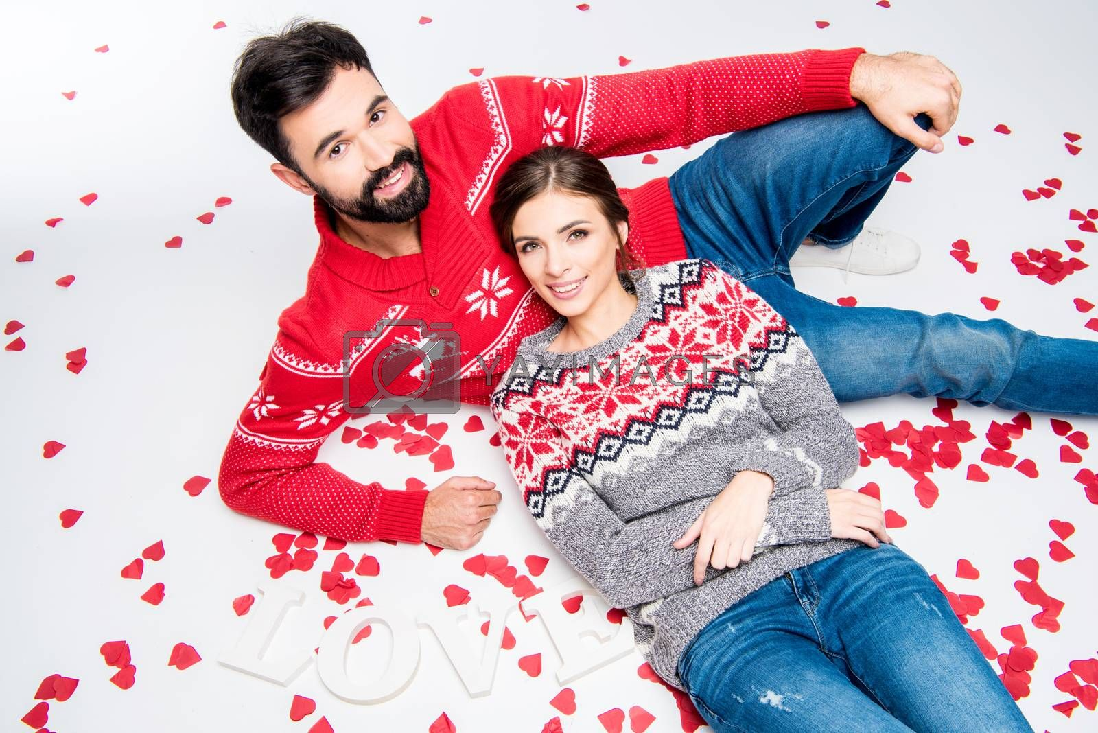 Loving couple lying together on white floor with pile of red hearts and word love