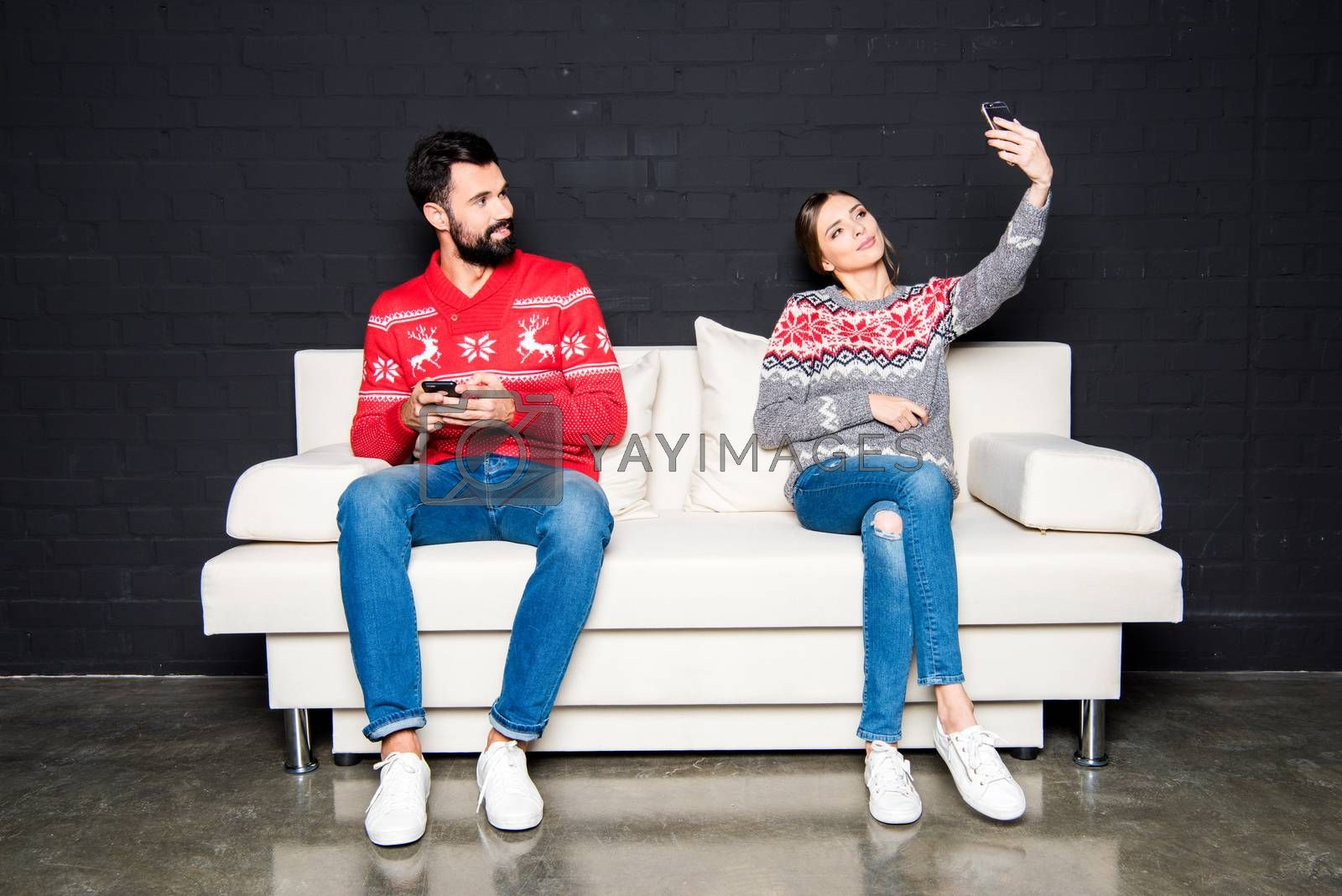 Young couple sitting on white couch and using smartphones, woman taking selfie
